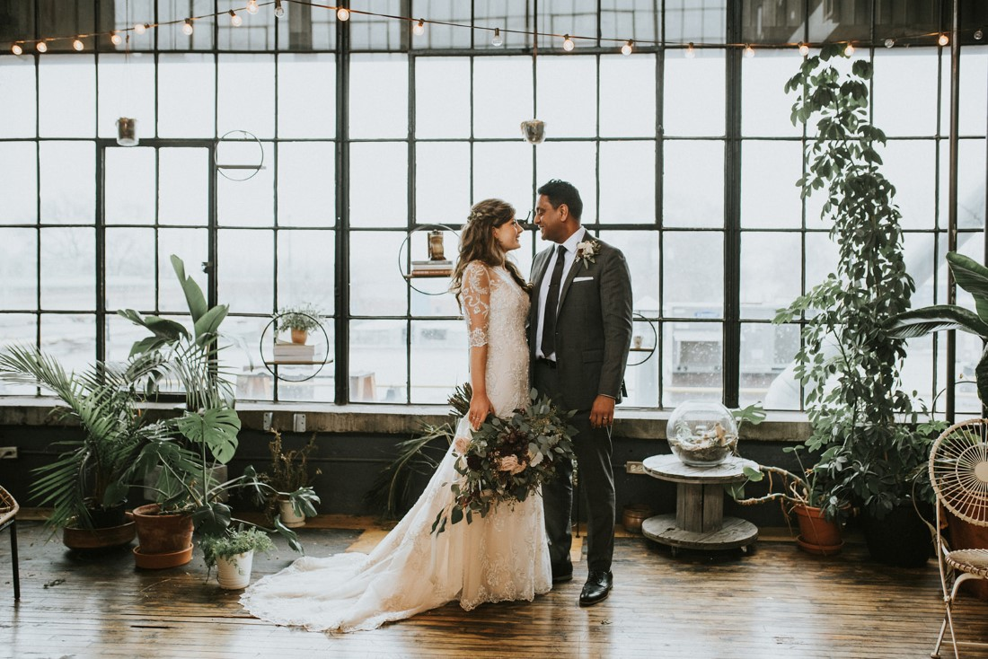 Snowy Urban Fairytale Wedding Couple in front of wall of windows and snow