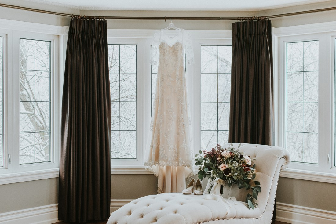 Maggie Sottero lace gown hangs in window while bouquet and shoes sit below on white lounge