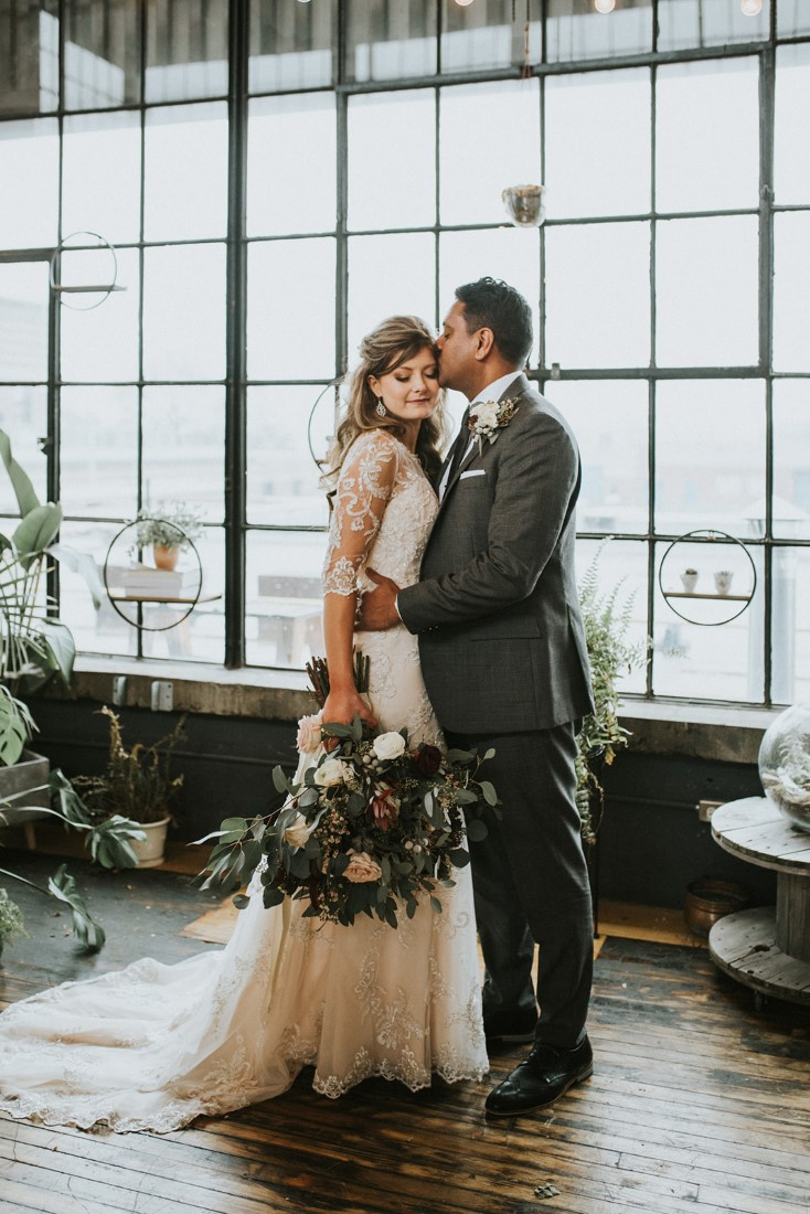Newlyweds in front of window panes and snow