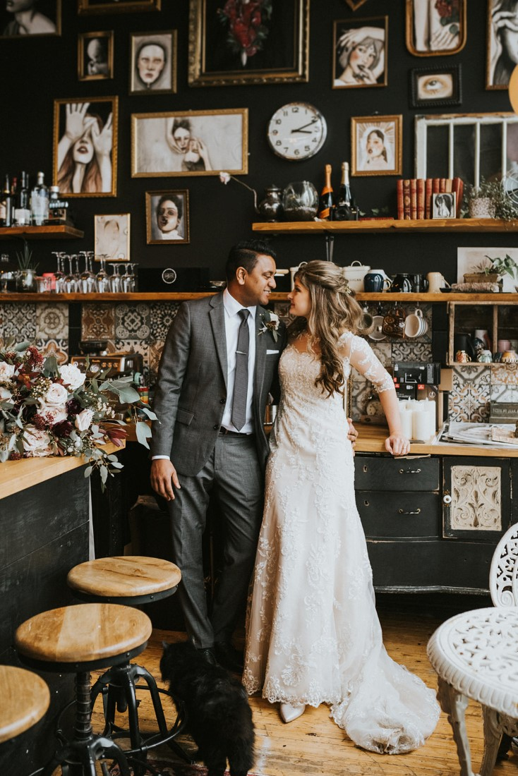Snowy Urban Fairytale Wedding couple in front of wall of antiques