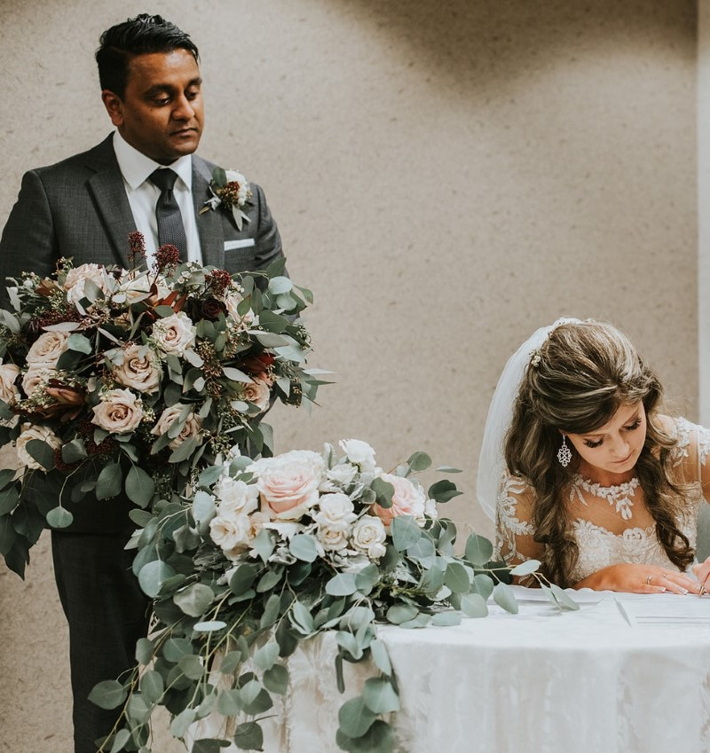 Bride signs register as groom holds her bouquet