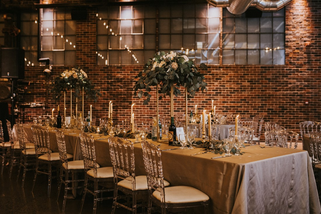 Clear Chiavari chairs at reception table featuring floral towers and grey linens