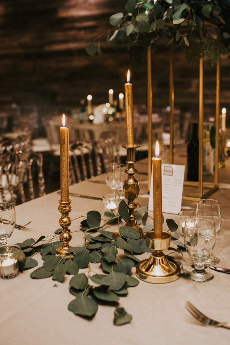 Vintage gold candlesticks on wedding table with grey eucalyptus