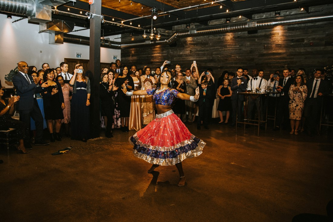 Indian girl in red skirt dances at fusion wedding