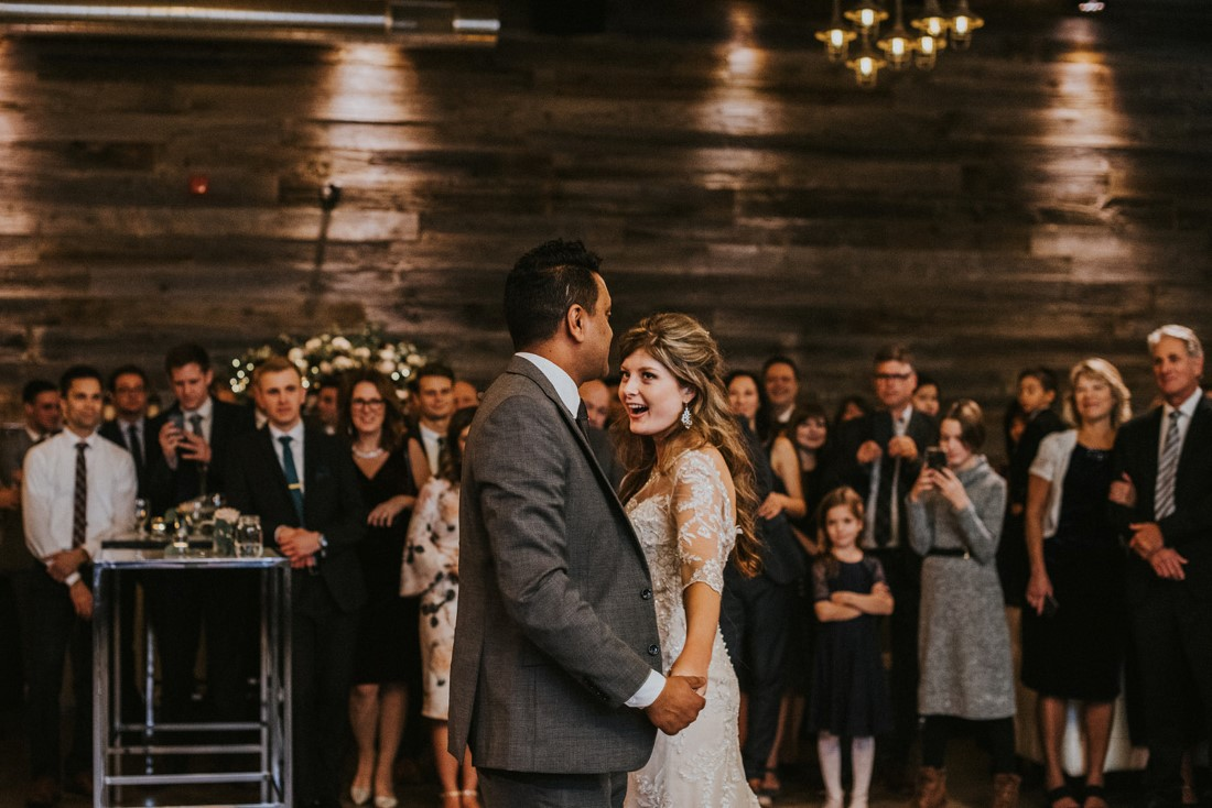 Newlyweds first dance in front of guests in urban warehouse venue