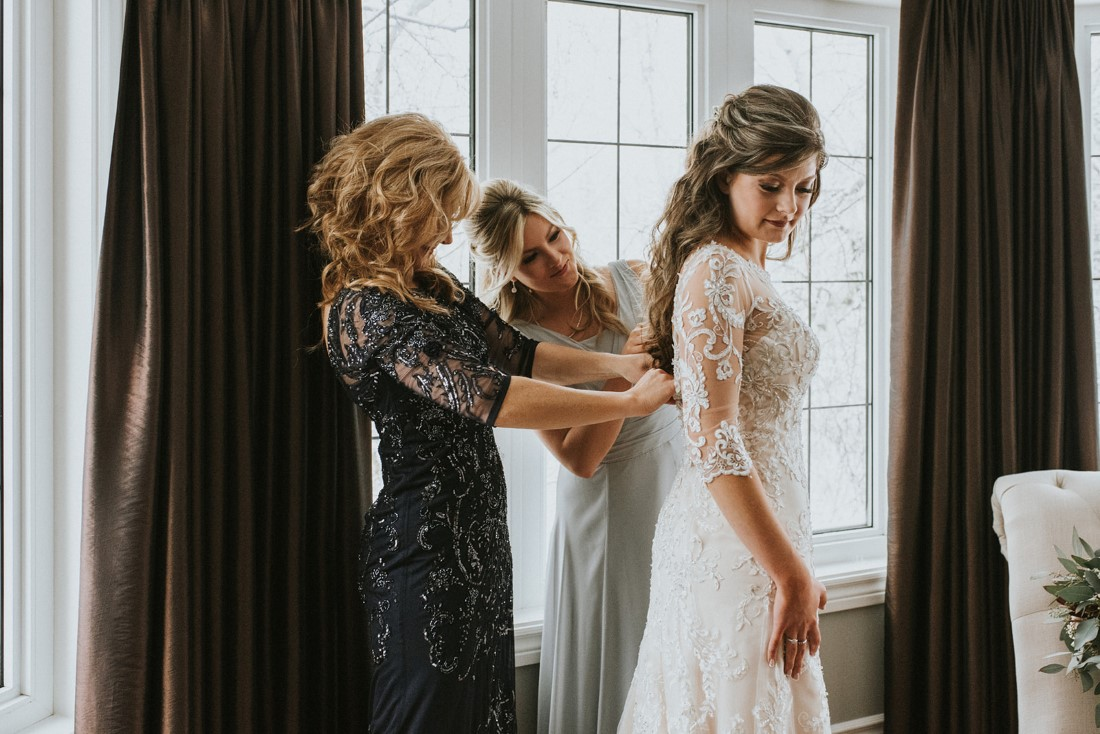 Mother and sister of bride help her with buttons on her Maggie Sottero gown