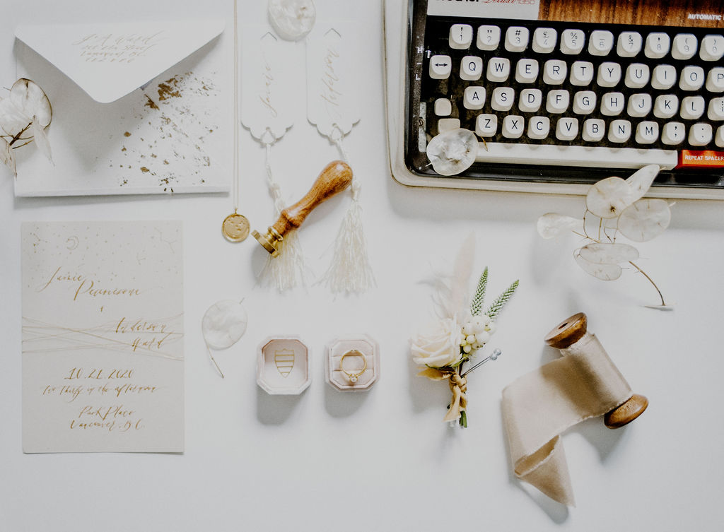 Astral Alignment Wedding Inspiration flat lay with antique typewriter, white roses boutonniere, wedding rings and ribbon by Sarah England Photography