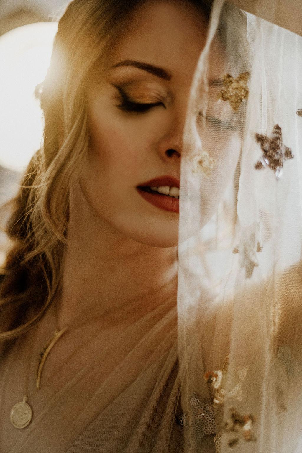 Bride holds sheer fabric of her Flutter Dress up against her face