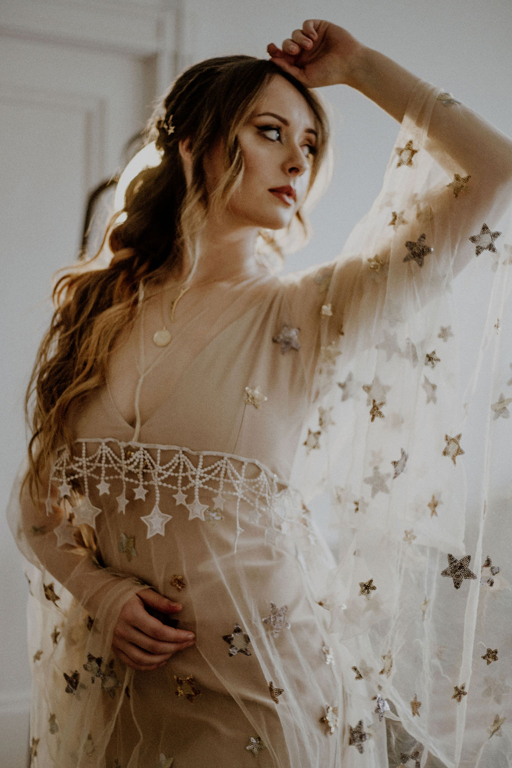 Bride shows off sheer butterly sleeves with gold stars on Flutter Dress Vancouver