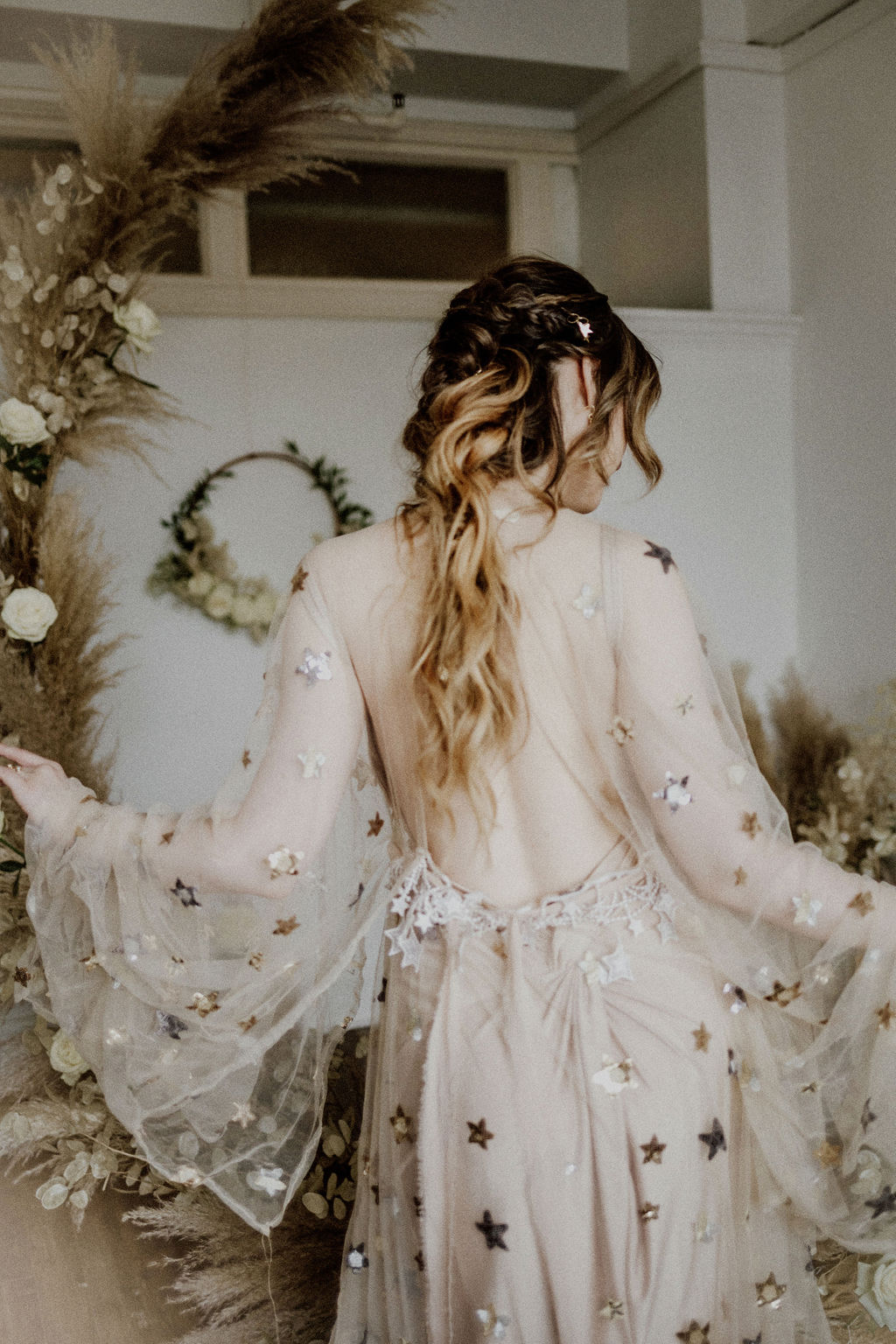 Bride wearing Flutter dress covered in gold stars with flowing sleeves and sheer back