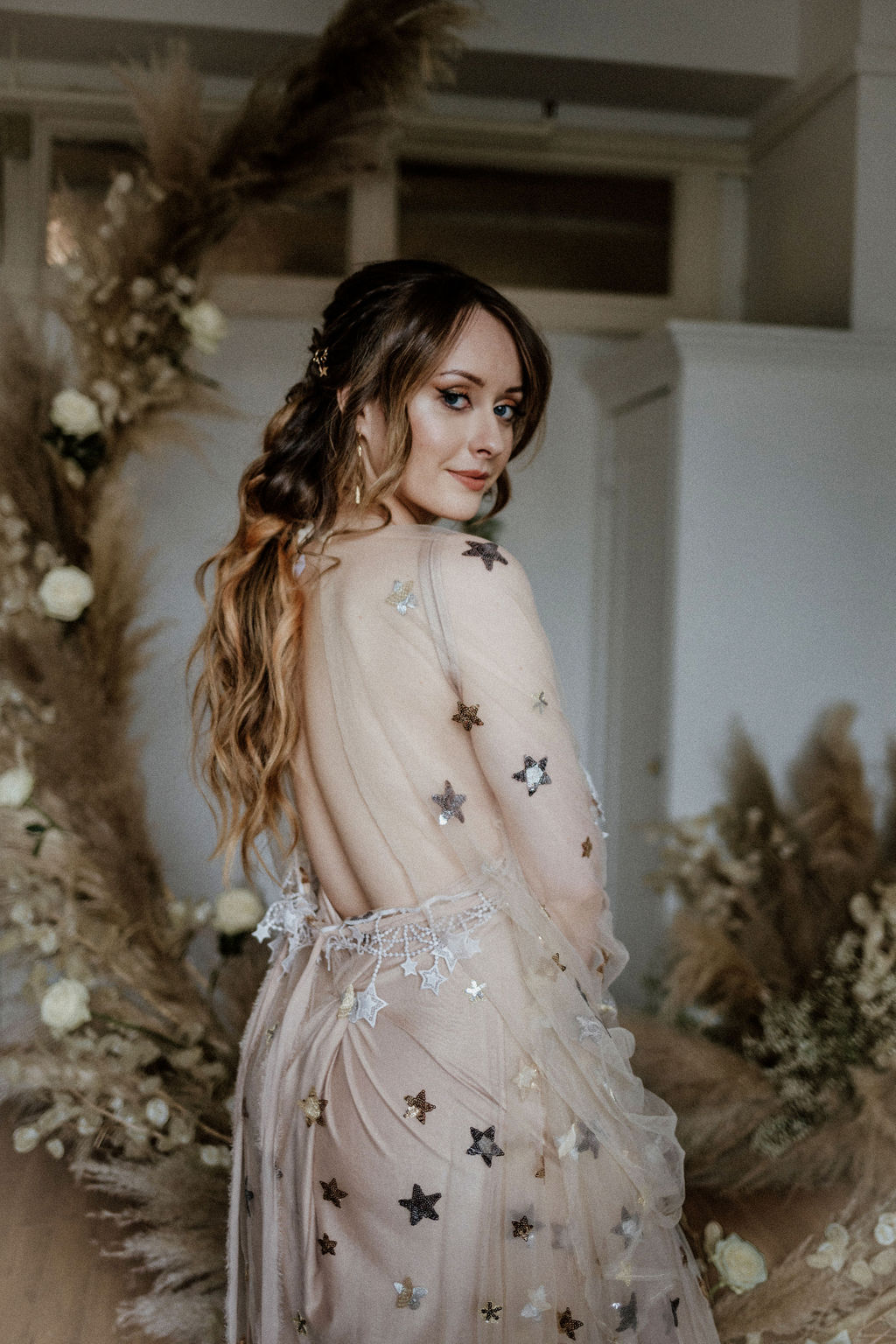 Bride wearing gold star gown by Flutters Dresses stands in front of pampas grass and white roses