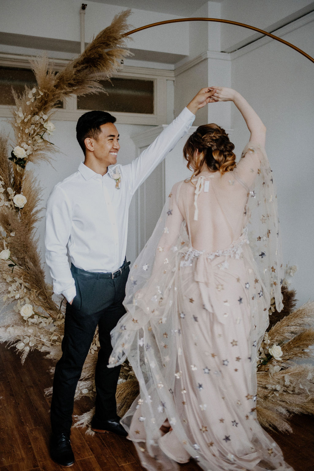 Groom twirls bride wearing dress covered in gold stars by Flutter Dresses