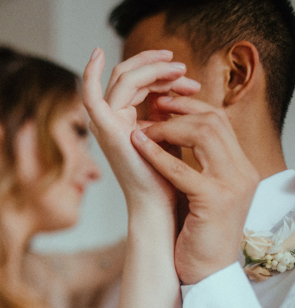 Bride and groom entwine hands by Sarah England Photography