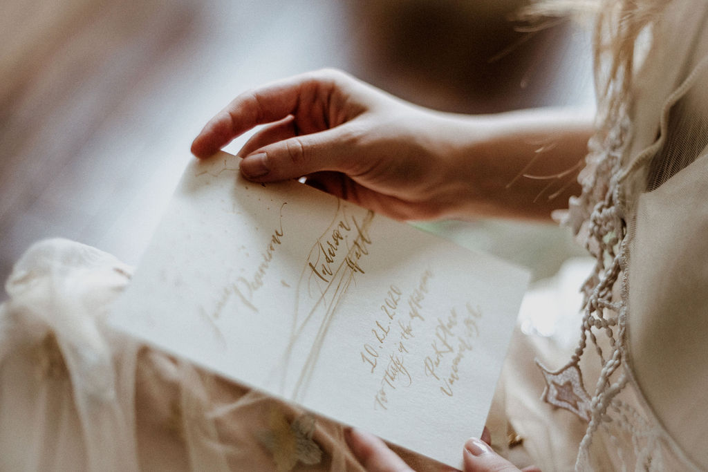 Bride looks at vows written in calligraphy by Penscription Vancouver