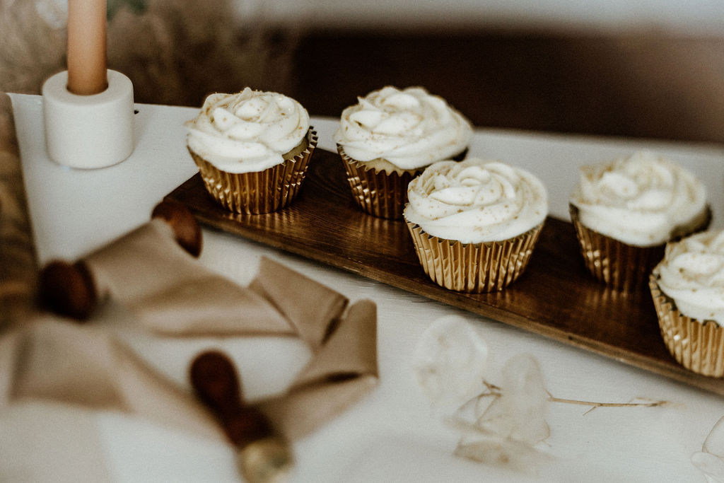 Cupcakes with white icing sit on wedding reception talbe by Baking with Aimes Vancouver