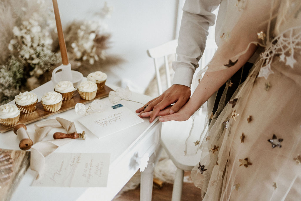 Bride and groom's hands show off wedding rings by cupcakes with white icing on reception table
