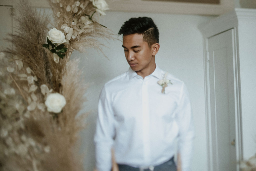Groom in white shirt in front of pampas grass and white roses wedding inspiration