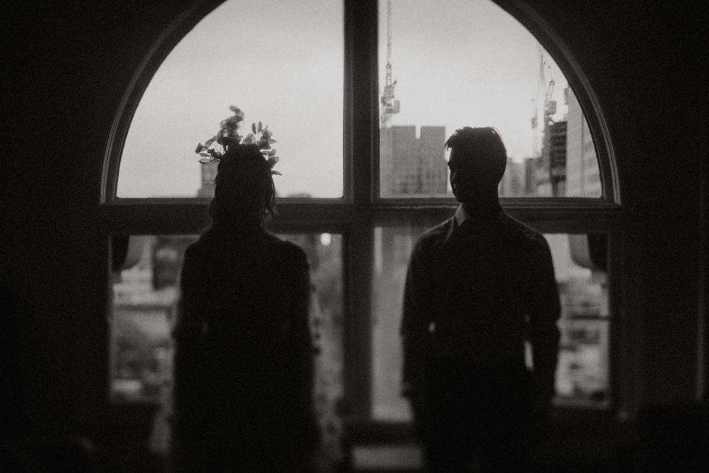 Bride and groom pose in silouette in front of Vancouver window in black and white