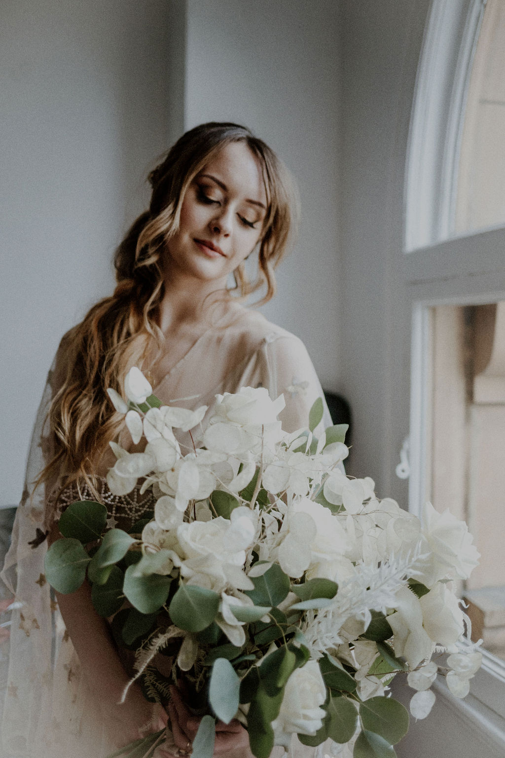 Bride holds bouquet of large white lillies by Van Simone Floral Vancouver