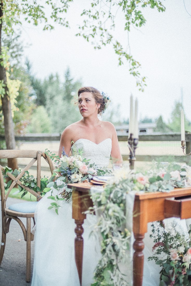 Bride sits at french country floral table in Vancouver