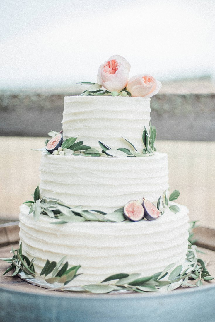 Three tiered wedding cake with greenery and blush pink roses by Taylor Made Cakes