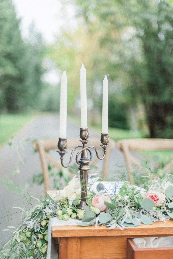 Gold candalabra with white candles surrounded by blush pink floral