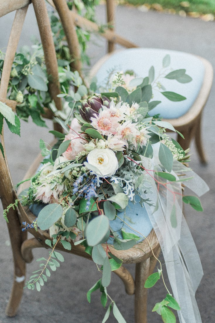 Blush pink flowers and ribbons sit upon blue french chairs