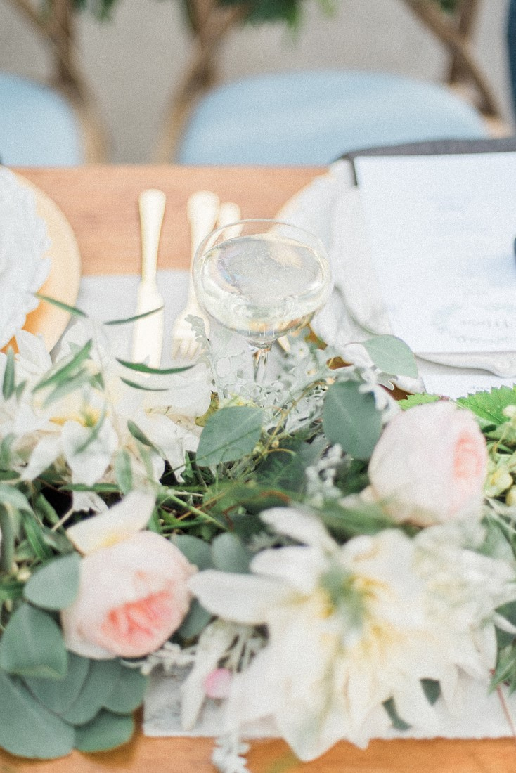Sweetheart table wedding decor of blush pink roses and greenery