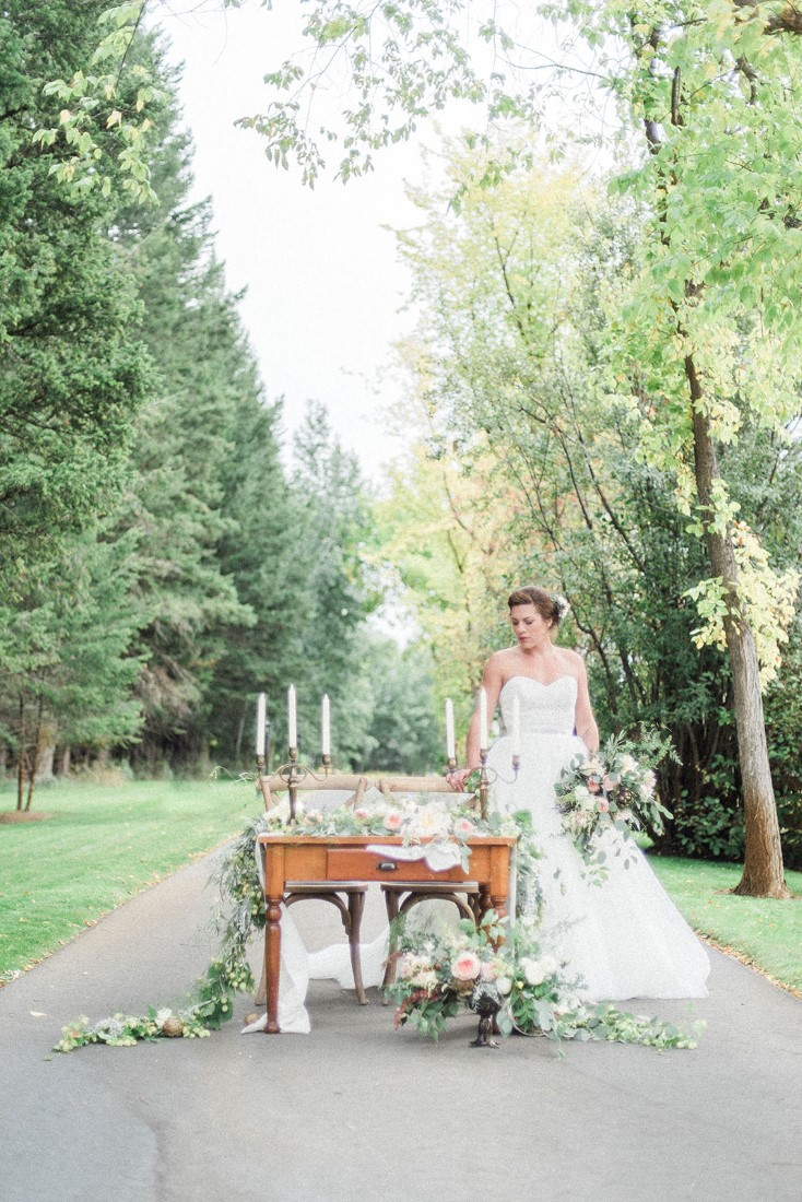 Bride stands on country road beside table filled with wedding decor