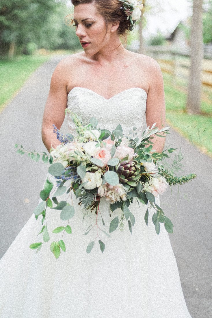 Bride holds bouquet of blush pink and white flowers on country road