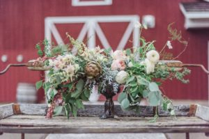 Bridal bouquets sit in front of red wood barn in Vancouver