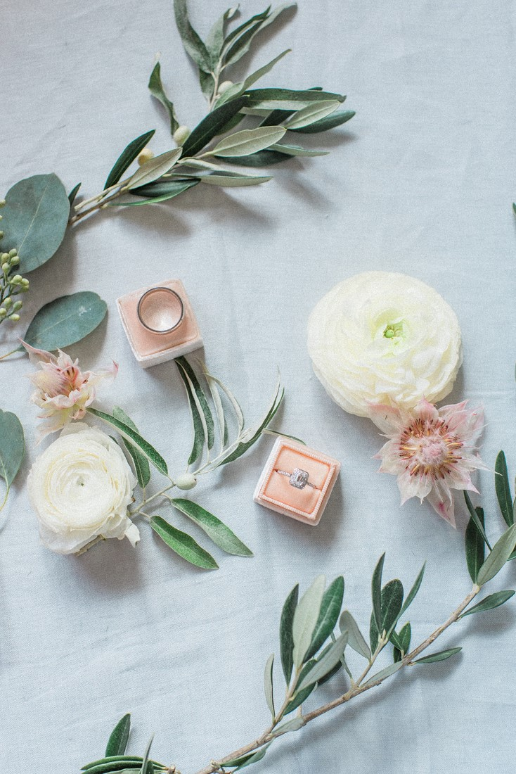Engagement Ring in pink velvet box surrounded by white roses and greenery