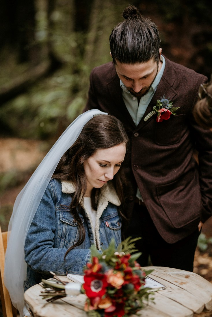 Bride wearing jean jacket signs wedding ceremony papers at Wick Inn Tofino