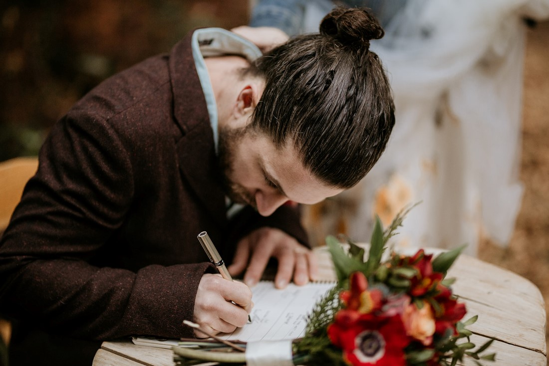 Groom signs paperwork after wedding ceremony at Wick Inn Tofino