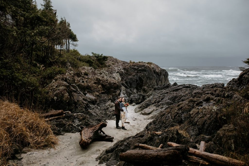 Bride and groom walk through beach rocks at Tofno