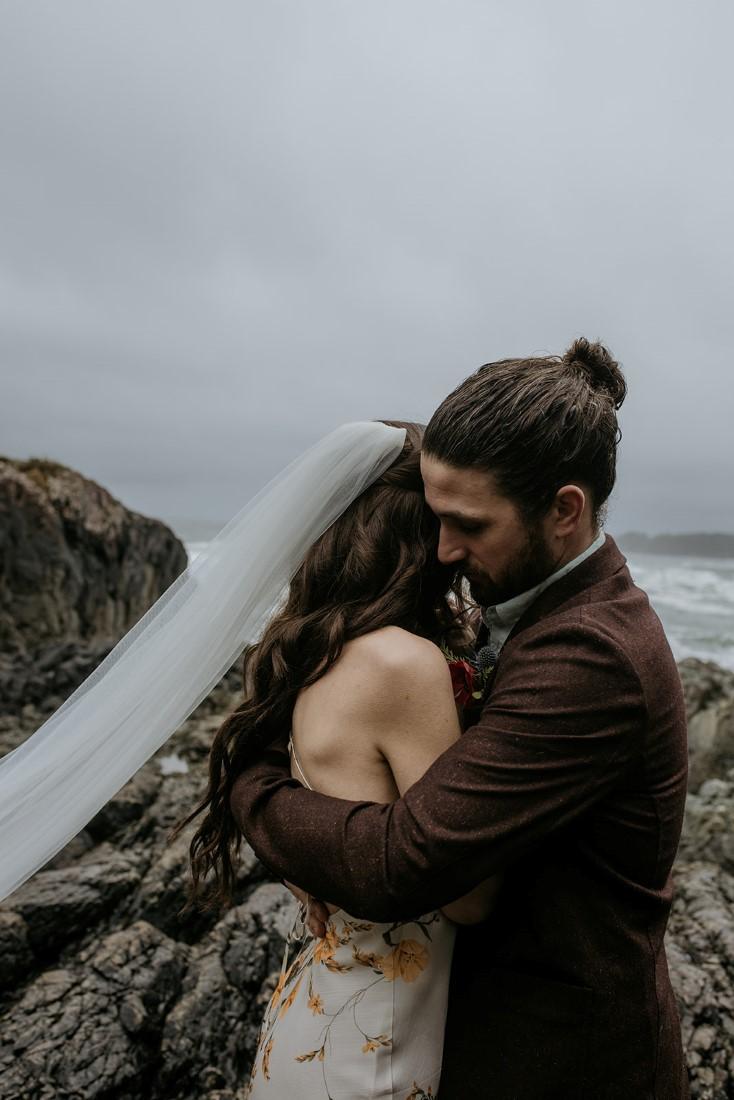 Bride and groom hug on the rocks of Chesterman Beach Tofino
