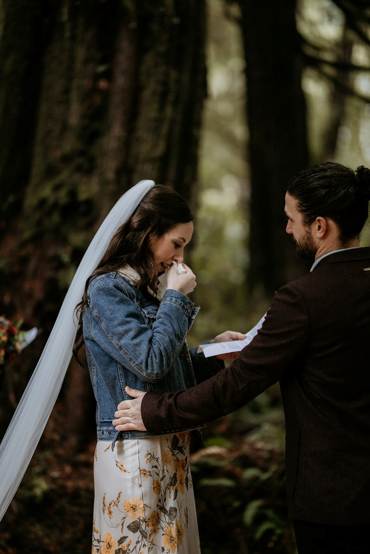 Bride weeps while sharing wedding vows during forest ceremony