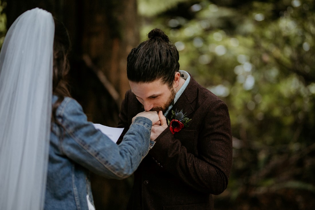 Groom kisses bride's hand during wedding ceremony in Tofino forest