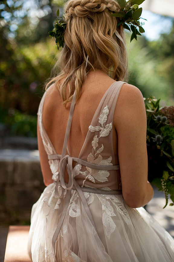 Bride shows off back details of Willowby by Watters gown