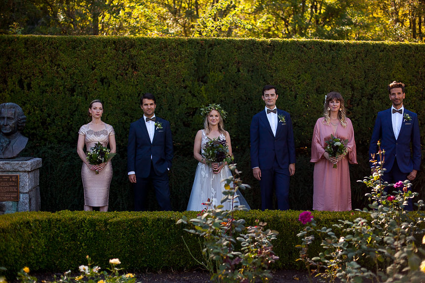 Wedding Party stands against tall green hedge