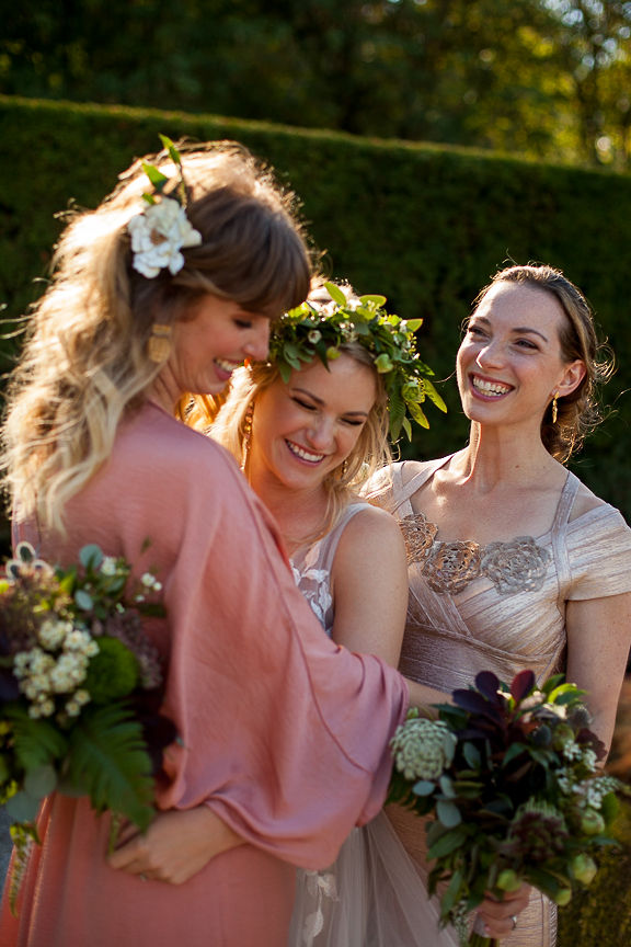 Bride and bridesmaids laugh and
