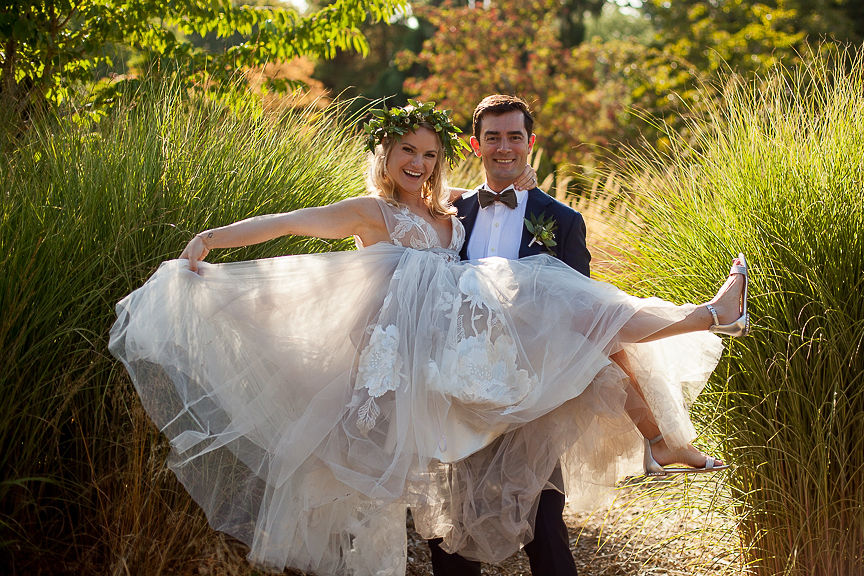 Groom carries bride in his arms and bride twirls her skirt
