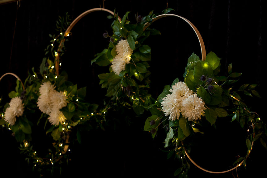 Gold hoops with white dahlias and greenery on black curtain by Flower Factory