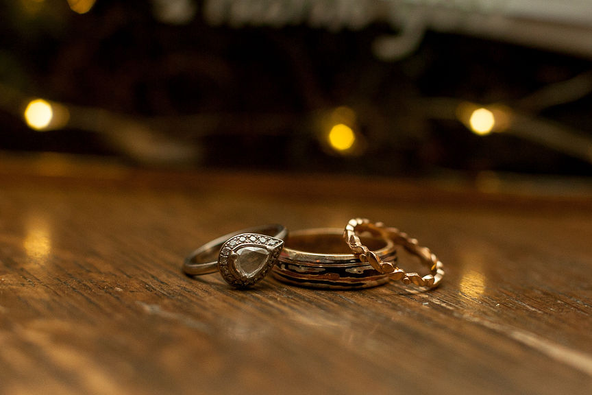 Wedding rings sit on table with twinkle lights behind