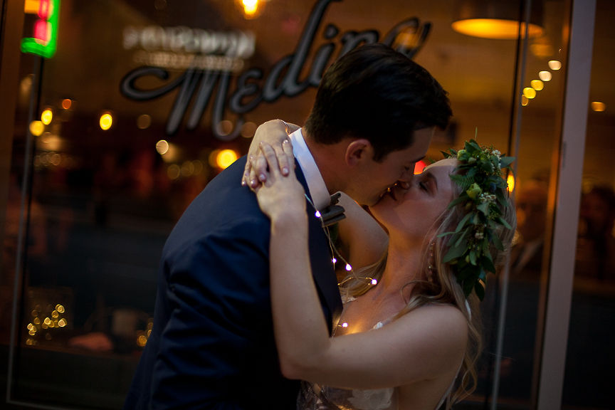 Romantic Wedding Day Newlyweds kiss under twinkle lights in Vancouver