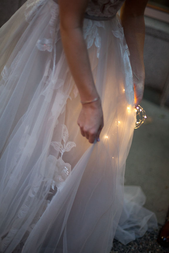 Bride holds sparkler against her Willowby by Watters wedding gown in Vancouver