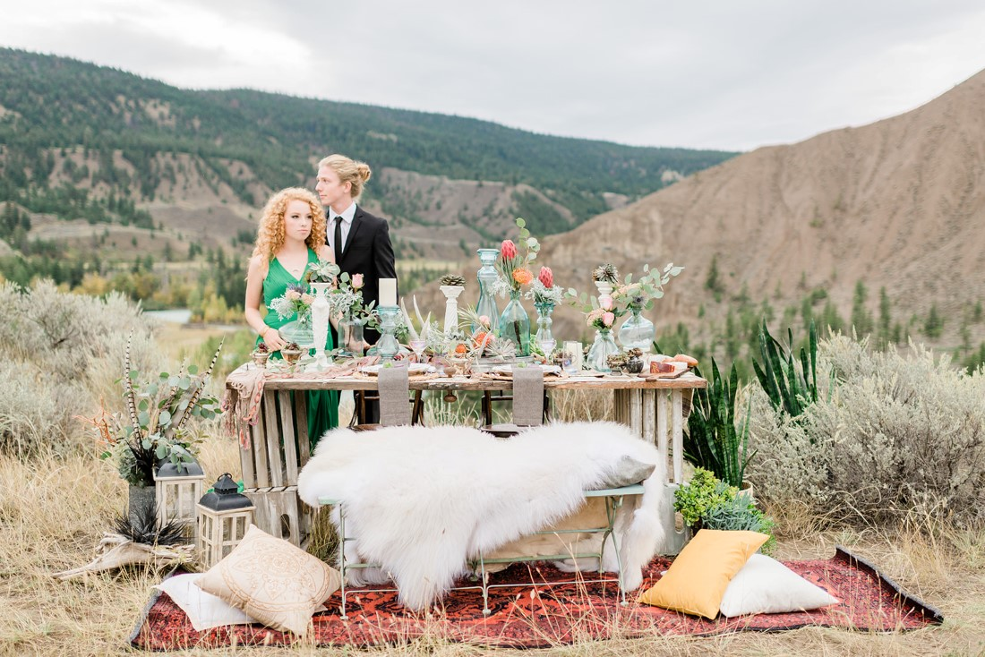 Ciouple stands behind boho tablescape with coloured glass bottles and white fir