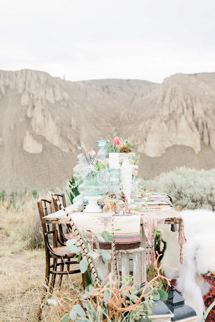 Tablescape with two brown chairs and a white fur sits by lake near Vancouver