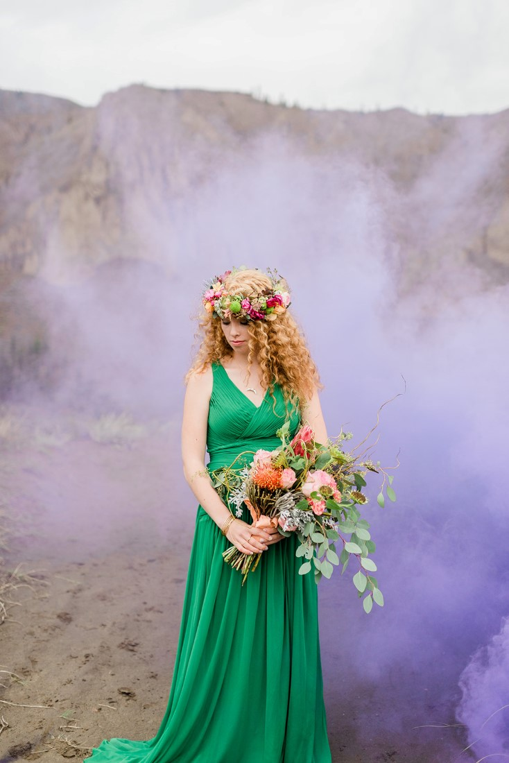 Bride in emerald green gown holds bouquet with purple smoke behind her
