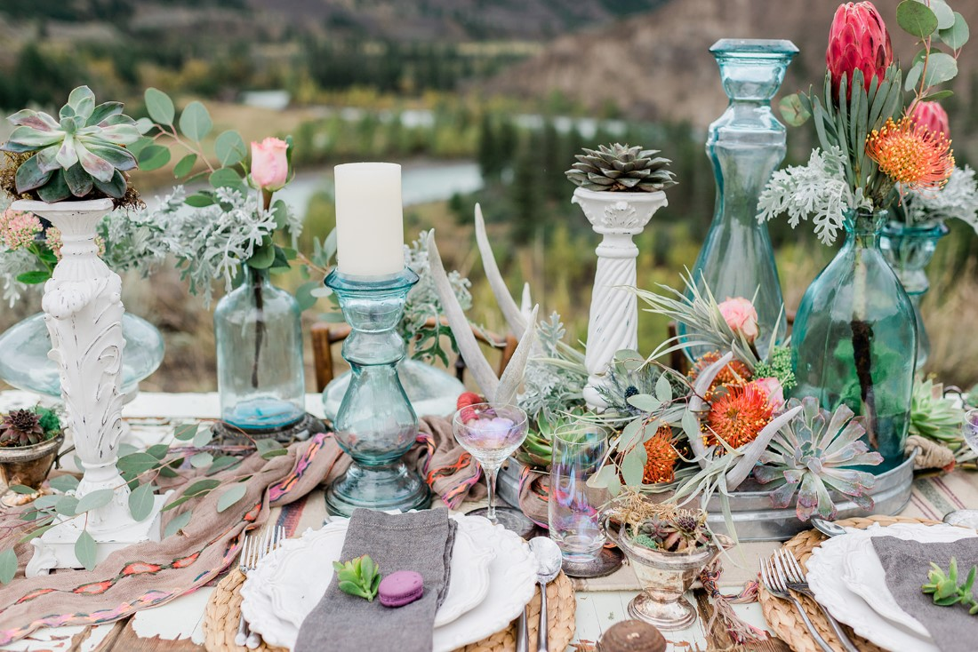 Boho inspired tablescape filled with orange flowers and candles